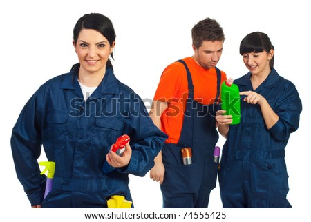 Cheerful cleaning worker woman in front of camera and her team having conversation in background