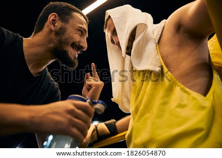 Cheerful coach sticking his finger up while instructing a fighter with a white towel on his head stock photo