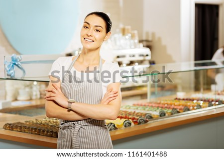 Cheerful confectioner. Cheerful confident confectioner standing near the shop window and smiling while feeling satisfied with her work