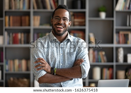 Cheerful confident handsome african american young adult businessman professional teacher hipster entrepreneur laughing looking at camera standing arms crossed at home office, business portrait
