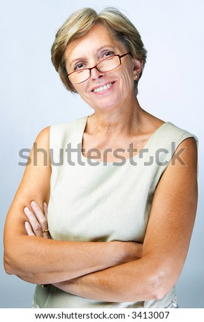 Cheerful confident mid adult woman with her arms crossed, studio shot