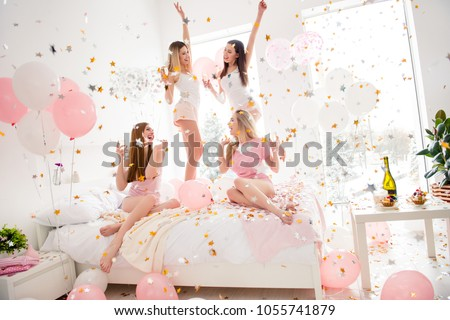 Cheerful, cool, sexy, pretty, charming, funky girls in night wear enjoying rain of colorful stars, confetti having theme party meeting indoor, drinking alcohol, dancing, laughing