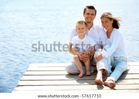 Cheerful couple and their little son relaxing on summer vacation - stock photo
