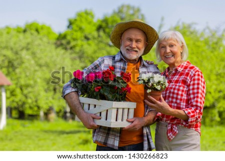 Cheerful couple. Cheerful aged husband and wife smiling broadly standing with flower pots