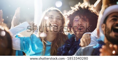 Cheerful couple cheering at a live soccer match. Group of people in the stadium cheering argentina football team.