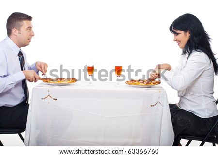 Cheerful couple eating pizza , sitting at table together and having conversation