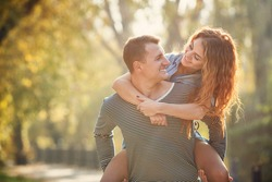 Cheerful couple having fun on summer vacation. Portrait of a happy couple laughing at camera. Young couple in the countryside in autumn. couple having fun outdoor in summer park.