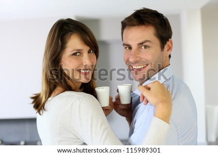 Cheerful couple holding cups of coffee