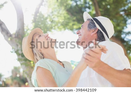Cheerful couple holding hands against trees