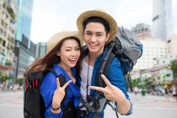 Cheerful couple in city showing thumbs up. Happy loving couple.