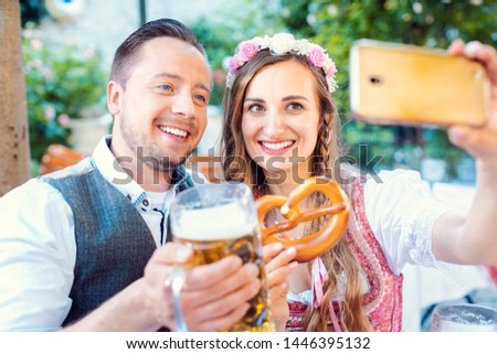 Cheerful couple in German beer garden taking a selfie picture with the phone