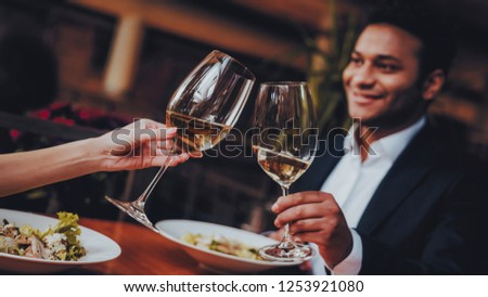 Cheerful Couple in Love Dating in Restaurant. Romantic Couple in Love Dating. Cheerful Man and Woman Couple Having Romantic Evening in Restaurant. Romantic Concept. Cheers Classes White Wine.