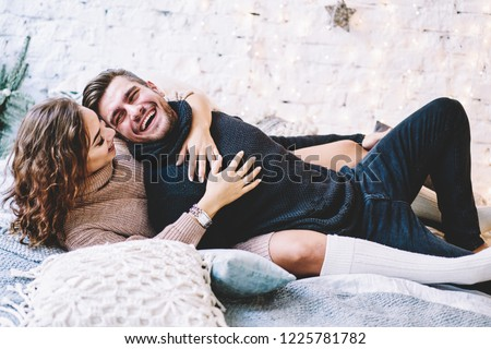 Cheerful couple in love dressed in knitwear having fun lying on cozy bed and laughing , carefree woman hugging her boyfriend spending winter holidays at home in warm and romantic atmosphere