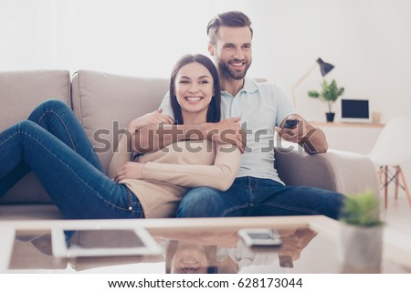 cheerful couple is watching tv...
