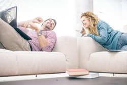 Cheerful couple lying on the couch and looking at laptop computer - Partners talking and smiling while relaxing in the living room, domestic life scene