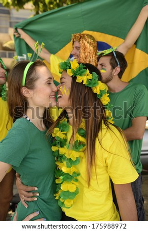 Cheerful couple of Brazilian girlfriends soccer fans almost kissing each other celebrating victory.