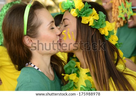 Cheerful couple of Brazilian girlfriends soccer fans kissing each other celebrating.