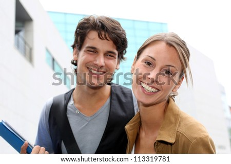 Cheerful couple of students standing on college campus