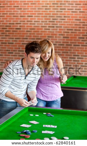 Cheerful couple playing cards on a billiard in a snooker club - stock photo
