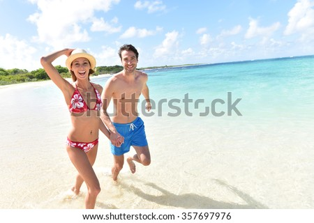 Cheerful couple running on a white sandy beach #357697976