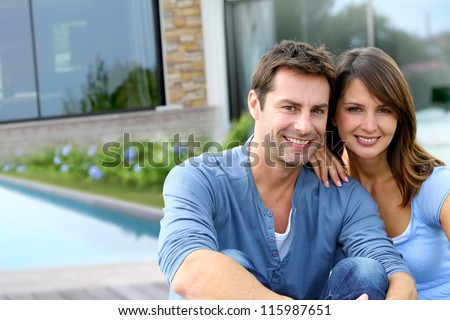 Cheerful couple sitting in front of new house