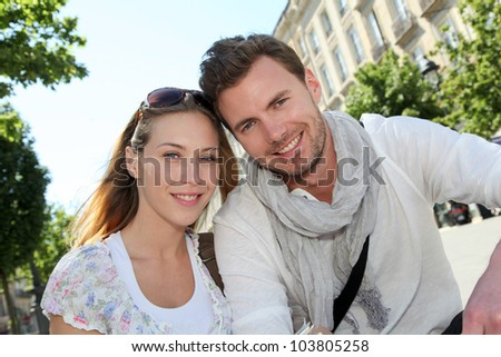 Cheerful couple sitting on a public bench in town