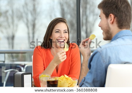 Cheerful couple talking and eating chip potatoes looking each other dating inside a coffee shop with an exterior background stock photo