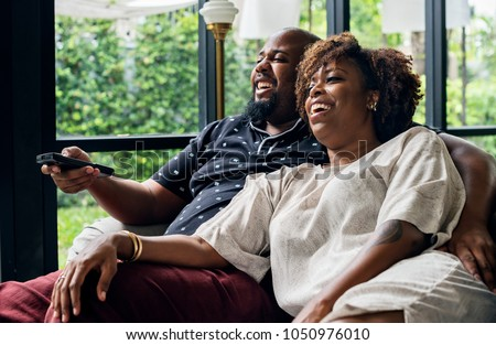 Cheerful couple watching TV together