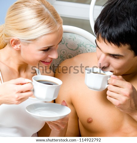 Cheerful couple with cups of coffee, indoor