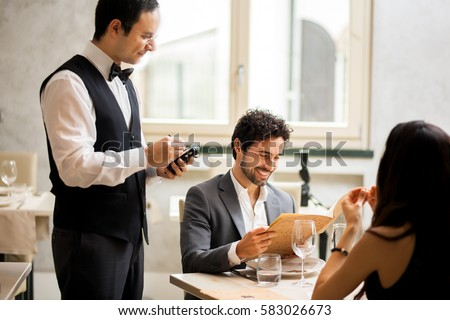 Cheerful couple with menu in a restaurant making order #583026673