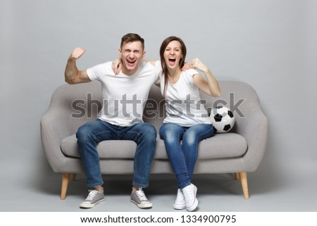 Cheerful couple woman man football fans cheer up support favorite team with soccer ball, hugging, clenching fists isolated on grey background. People emotions, sport family leisure lifestyle concept #1334900795
