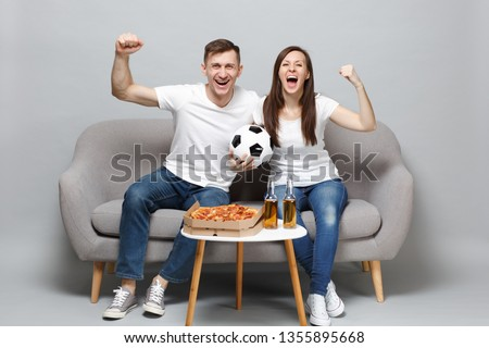 Cheerful couple woman man football fans in white t-shirt cheer up support favorite team with soccer ball, clenching fists isolated on grey background. People emotions, sport family lifestyle concept #1355895668