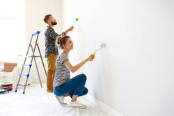 Cheerful couple young  man and woman smiling and  painting white wall with roller during renovation in new apartment