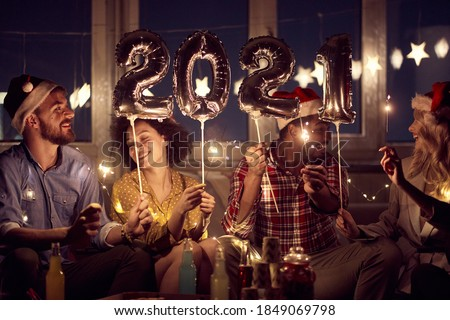 Cheerful couples having good time together at New Year eve home party in festive atmosphere. New Year, home party, friends time together