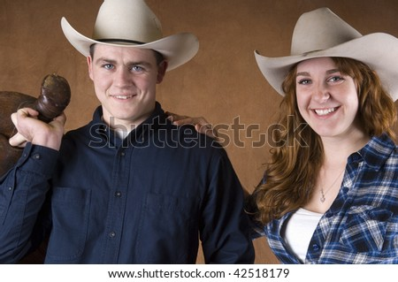 Cheerful Cowboy and Cowgirl couple in studio