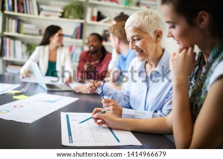 Cheerful coworkers in office during company meeting #1414966679