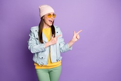 Cheerful crazy girl promoter point index finger copyspace indicate adverts promo, discount recommend choice decision advice wear green yellow trousers isolated purple color background
