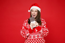 Cheerful crazy young Santa woman 20s wearing sweater Christmas hat biting eating chocolate bar isolated on bright red wall background studio portrait. Happy New Year celebration merry holiday concept