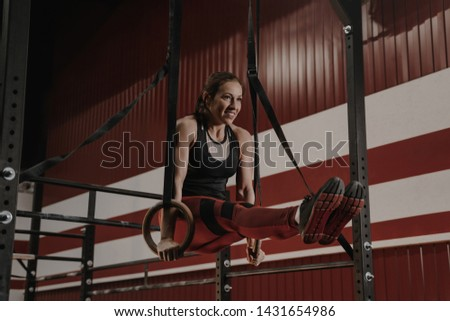 Cheerful crossfit woman doing abs exercises on gymnastic rings. Female athlete works on her abdomenal muscles during workouts at the gym.