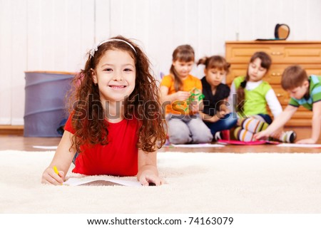 Cheerful curly girl laying on carpet with pencil
