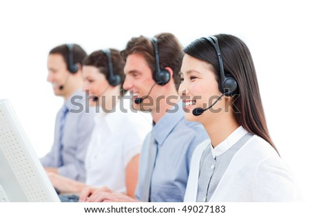 Cheerful customer service agents working in a call center against a white background