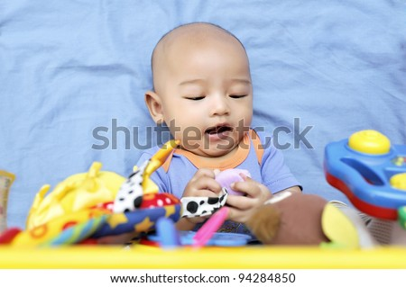 Cheerful cute baby boy playing with hanging toys.