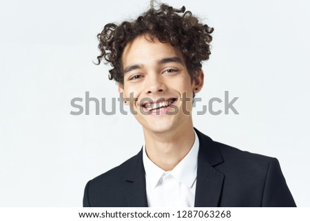 cheerful cute curly man in dark suit on gray background isolated #1287063268