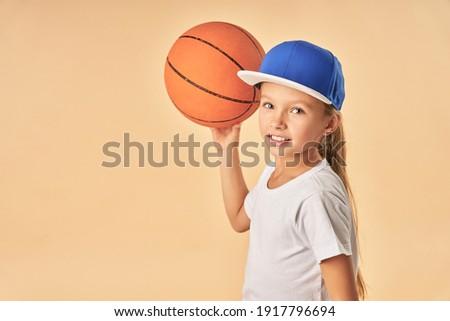 Cheerful cute girl in cap plying basketball
