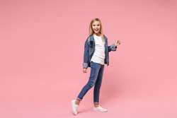 Cheerful cute little blonde kid girl 12-13 years old in denim jacket isolated on pastel pink wall background children studio portrait. Childhood lifestyle concept. Mock up copy space. Looking camera