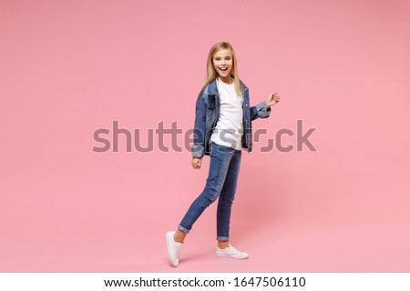 Cheerful cute little blonde kid girl 12-13 years old in denim jacket isolated on pastel pink wall background children studio portrait. Childhood lifestyle concept. Mock up copy space. Looking camera Stock photo ©