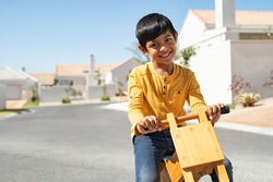 Cheerful cute little boy on wooden balance cycle and smiling while looking at camera. Happy indian child riding bike on road with copy space. Portrait of cute ethnic kid learning to drive bicycle.