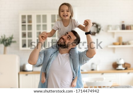 Cheerful dad carrying on neck playing with happy little preschool child daughter indoors. Playful small kid girl having fun with smiling bearded father at home, good family relations concept.