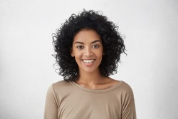 Cheerful dark-skinned girl smiling broadly, rejoicing at her victory in competition among young writers, standing isolated against grey wall background. People, success, youth and happiness concept