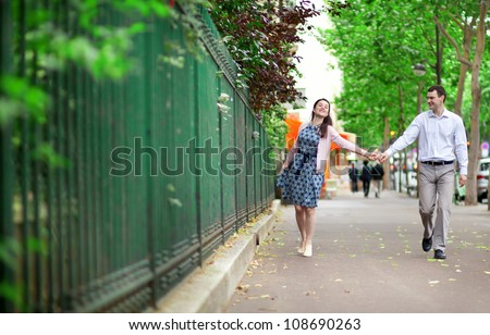 Cheerful dating couple is walking in Paris